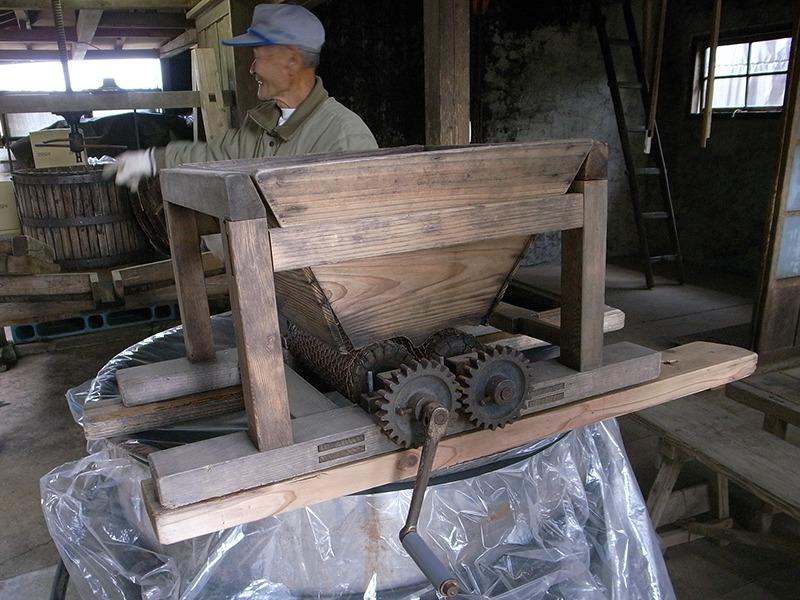 ぶどうの破砕機と貞夫さん。年季の入った道具はアンティーク家具のよう。